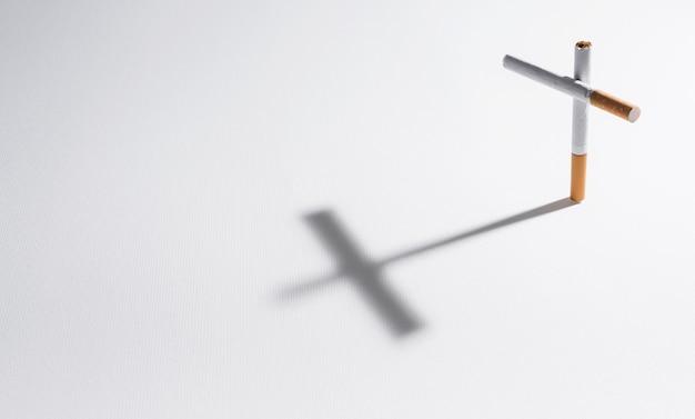 Um cigarro com sombra fazendo uma cruz