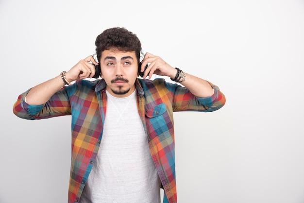 Um cineasta segurando uma claquete em branco e não consegue ouvir nada por causa do volume.