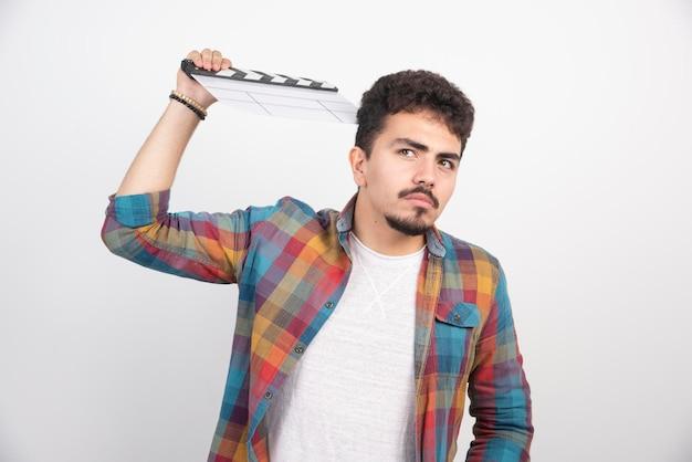 Um cineasta segurando uma claquete em branco e parece cansado e entediado.