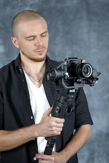 Um cinegrafista profissional segura uma câmera profissional em um estabilizador de cardan de 3 eixos