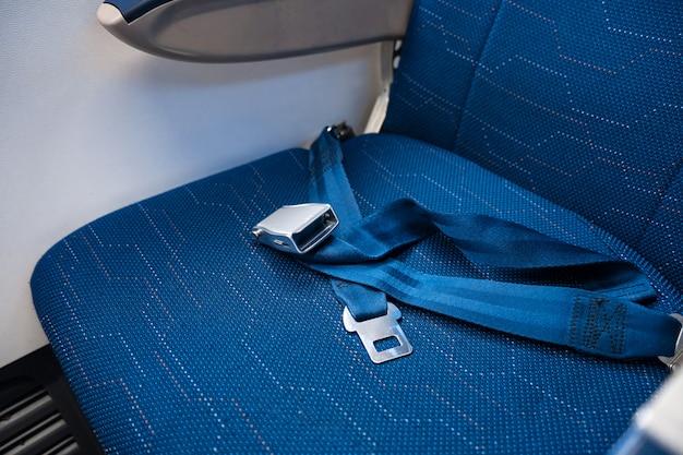 Um cinto de segurança desatado em um assento vazio em um avião. segurança em vôo