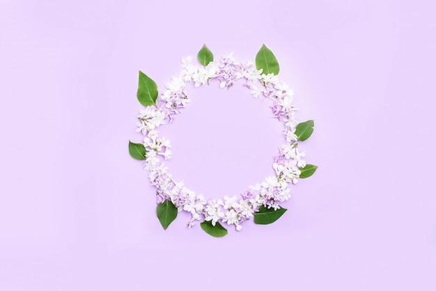 Um círculo de flores lilás e folhas, um lugar para texto.