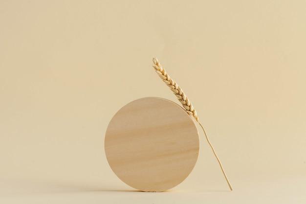 Um círculo de madeira e uma espiga de trigo em um fundo bege.