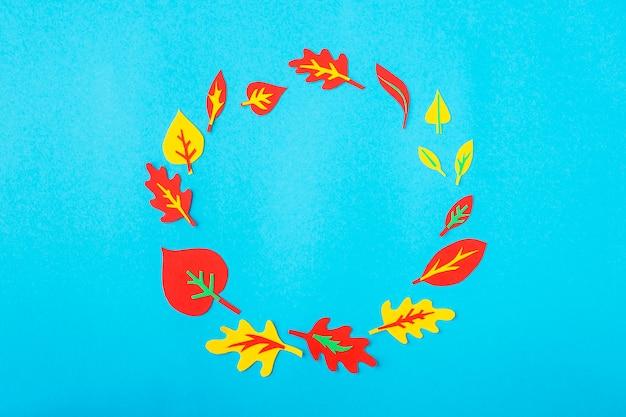 Um círculo feito de papel applique de folhas de outono em um fundo azul