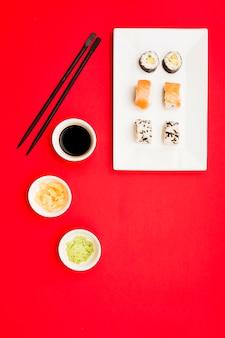 Um clássico filadélfia e sushi rolos com wasabi; gengibre e molho de soja na bandeja branca