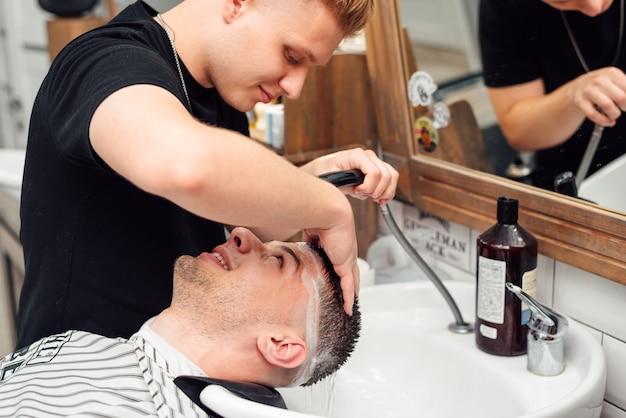 Um cliente do sexo masculino lava o cabelo em uma barbearia