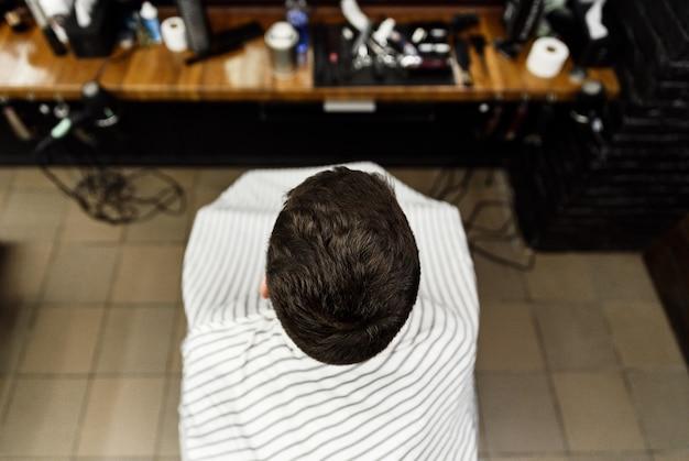 Um cliente em um salão de cabeleireiro muda seu penteado durante um corte de cabelo