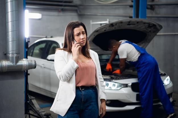 Um cliente está falando ao telefone. trabalhador da oficina em segundo plano consertando um carro