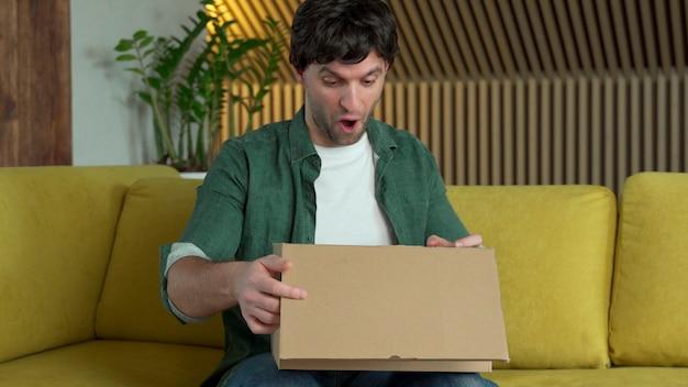 Um cliente humano recebe uma caixa de papelão aberta enquanto está sentado em um sofá amarelo em casa. homem feliz desempacota uma caixa com um pacote