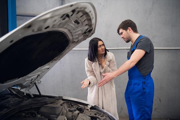 Um cliente reclama com um trabalhador sobre um reparo ruim do carro