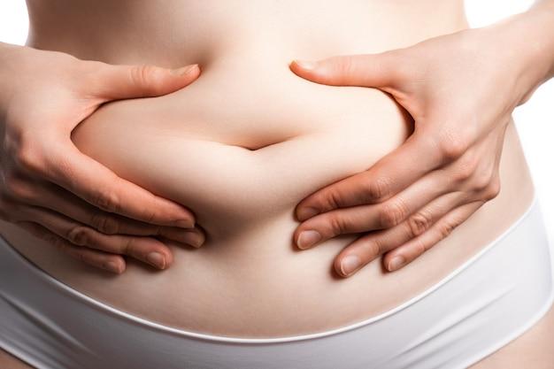 Um close da barriga feminina, que ela beliscou uma pequena camada de gordura no umbigo.