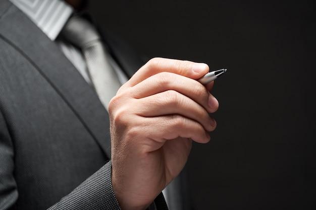 Um close da caneta na mão do empresário, terno cinza, parede escura backgrou