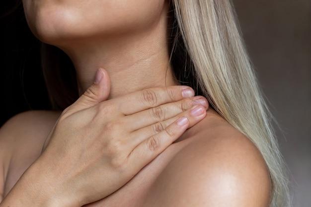 Um close da pele de uma jovem loira a menina usa um creme para hidratar a pele do pescoço