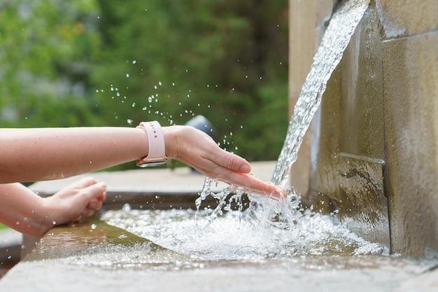 Um close das mãos da mulher, pegando o fluxo de água da fonte