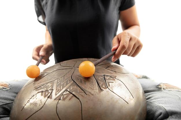 Um close das mãos tocando o hank drum