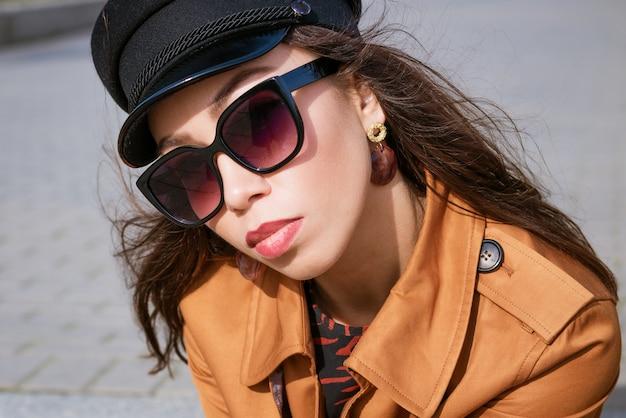 Um close de um portre feminino de aparência caucasiana em óculos de sol e boné preto olha para o quadro. linda mulher morena em um dia ensolarado de primavera