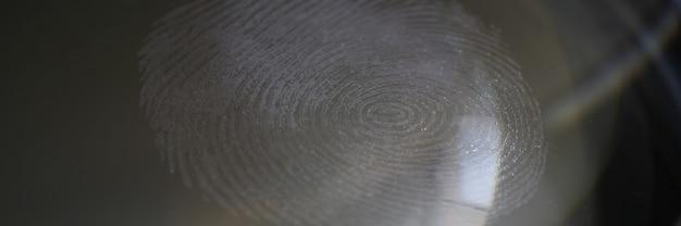 Um close de uma impressão digital em um vidro contra um fundo escuro. tecnologia moderna de biometria