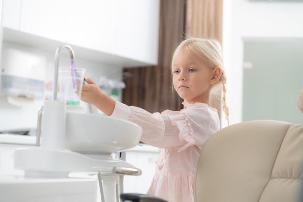 Um close de uma menina em um consultório de dentista. crianças que visitam o conceito de dentistas. conceito de saúde do dente