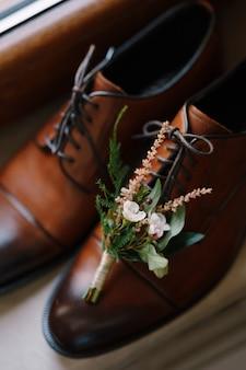 Um close dos botões para o noivo em sapatos de couro masculinos no parapeito da janela