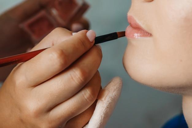 Um close dos lábios da mulher delicada enquanto visagiste segura um lápis atrás do rosto