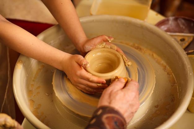 Um close-up da mão de um oleiro masculino que ensina seu aluno