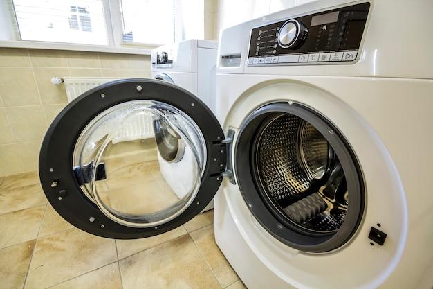 Um close-up da máquina de lavar roupa aberta no banheiro