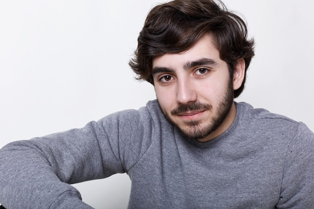 Um close-up de jovem hippie com olhos inteligentes escuros de barba e bigode isolado sobre a parede branca, tendo o resto dentro de casa
