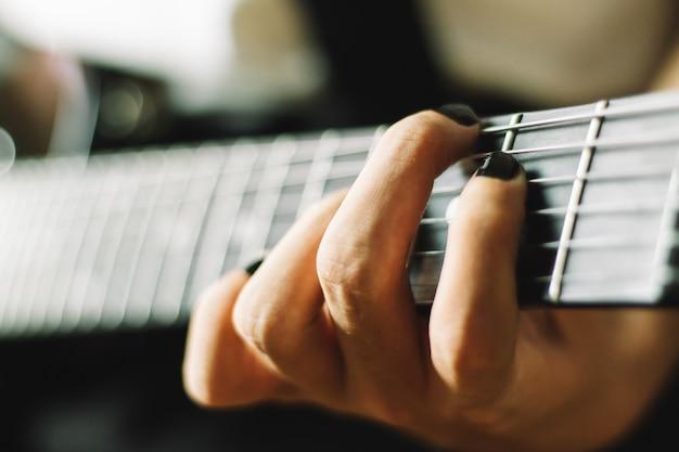 Um close-up de mão tocando violão