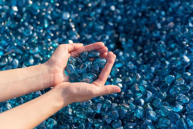 Um close up de pedras de cristal azuis na mão da mulher.