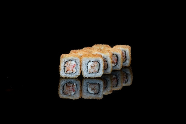 Um close up de rolinhos de sushi fritos isolados no reflexo preto