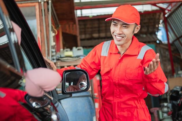 Um close-up de um homem asiático em uniforme vermelho cumprimenta com um gesto de boas-vindas quando um cliente chega de carro para consertar a oficina