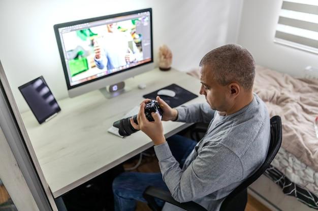 Um close-up de um homem que trabalha em uma agência de mídia que controla e monitora fotos com a câmera mais moderna