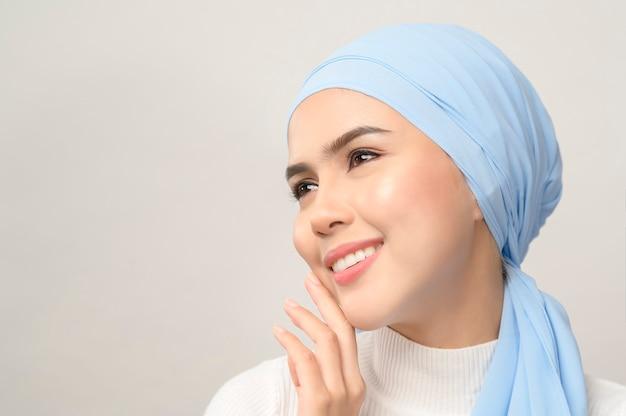 Um close-up de uma jovem e bela mulher muçulmana com um hijab isolado na parede branca