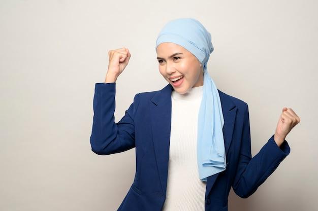 Um close-up de uma jovem mulher de negócios muçulmana bonita com um hijab isolado no estúdio de fundo branco