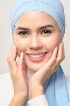 Um close-up de uma jovem mulher muçulmana bonita com hijab isolado no estúdio de fundo branco, conceito de cuidados com a pele de beleza muçulmana.