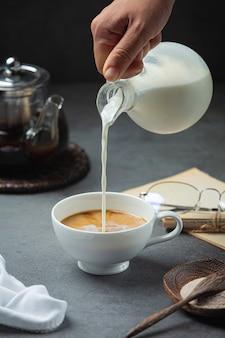 Um close-up de uma mão servindo água com café em uma xícara de café, conceito do dia internacional do café