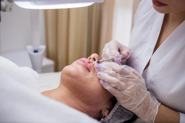 Um close-up do médico aumenta os lábios da cliente