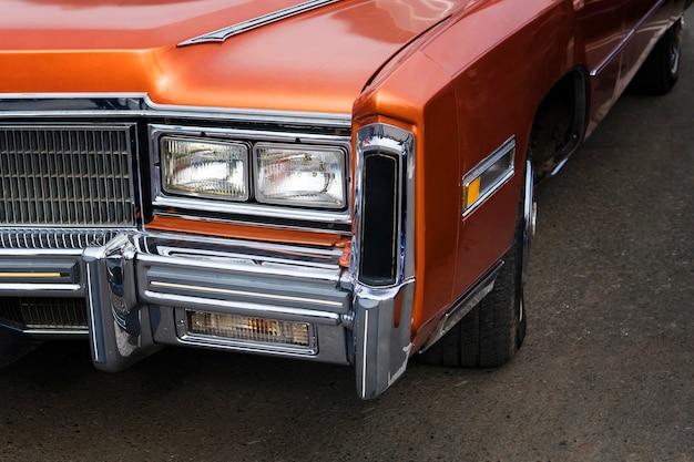 Um close up dos faróis e do pára-choque dianteiro de um automóvel americano antigo. carro polido e brilhante em uma exposição retrô dos 60-70 anos do século xx.