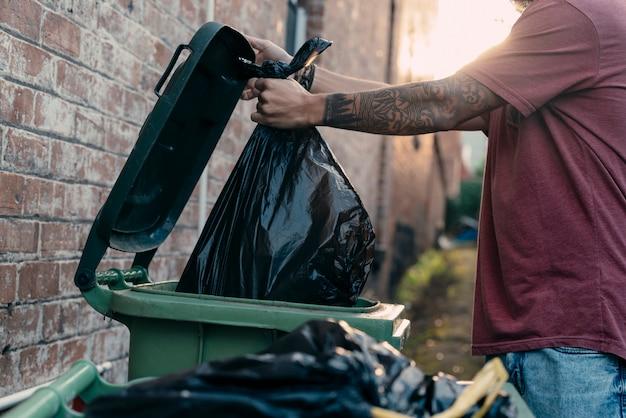 Um close-up foto de uma jovem mão masculina jogando lixo no lixo na rua