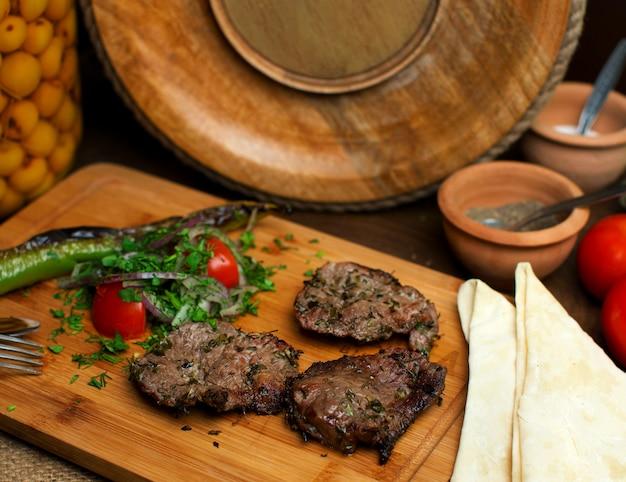 Um close-up frontal vista frito fatias de carne saborosa, juntamente com legumes frescos na mesa de madeira marrom