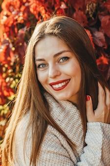 Um close-up retrato de uma mulher no fundo das folhas vermelhas e amarelas no parque. ela está tecendo um suéter bege e usa um batom vermelho. ela está sorrindo e arrumando seus longos cabelos.