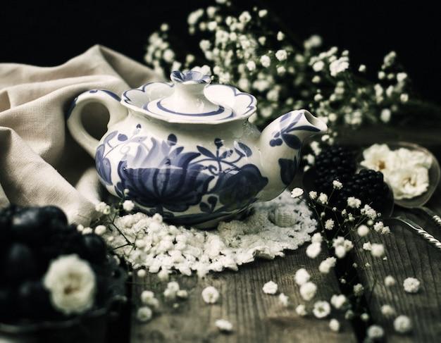 Um close-up vista frontal chaleira metálica projetada em torno de flores brancas no chão escuro