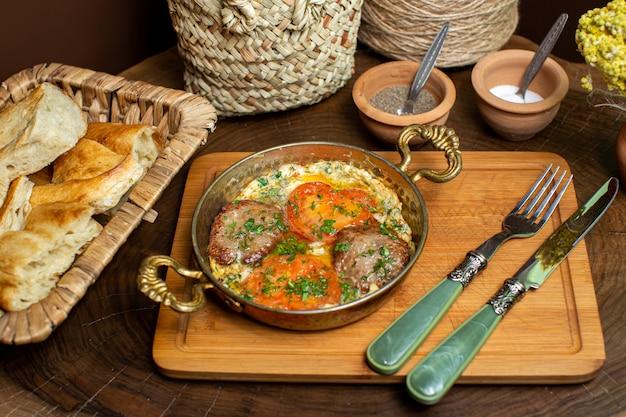 Um close-up vista frontal ovos de refeição com tomates vermelhos e fatias de carne, juntamente com talheres e fatias de pão