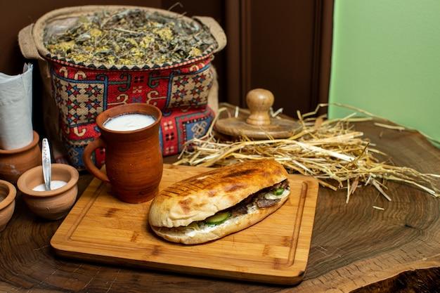 Um close-up vista frontal sanduíche chamado doner com carne e legumes cortados dentro junto com iogurte na superfície de madeira marrom