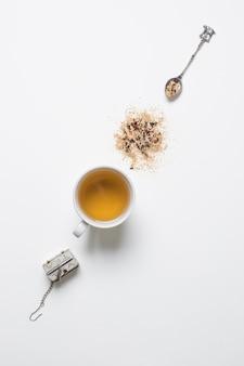 Um coador de chá antiquado; colher com ervas e chá na xícara em pano de fundo branco