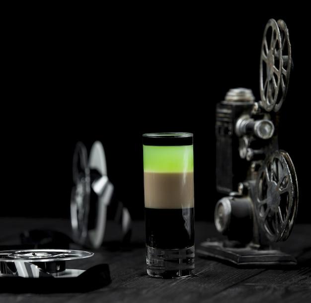 Um cocktail de álcool colorido sobre uma mesa rústica.
