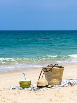 Um coco novo fresco está pronto para comer e um saco da palha e um chapéu de palha das mulheres na toalha em uma praia arenosa contra um mar azul. conceito de viagens de férias tropicais. espaço da cópia