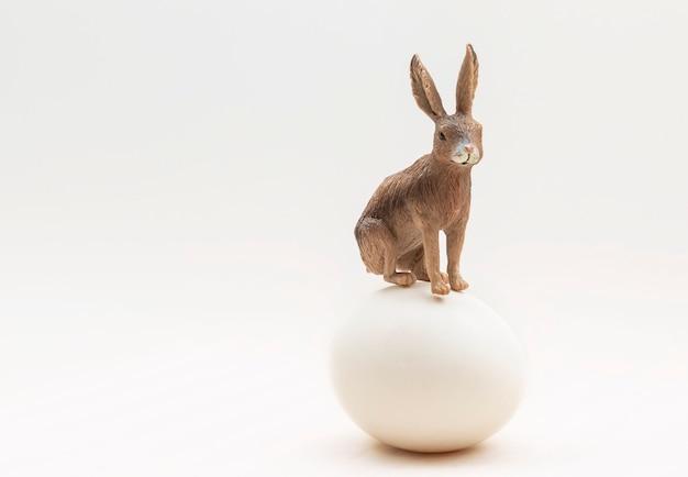 Um coelhinho da páscoa pousado sobre um ovo de galinha isolado em um fundo branco