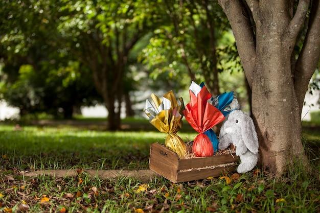Um coelho de pelúcia segurando uma cesta de ovos de páscoas brasileiras debaixo de uma árvore