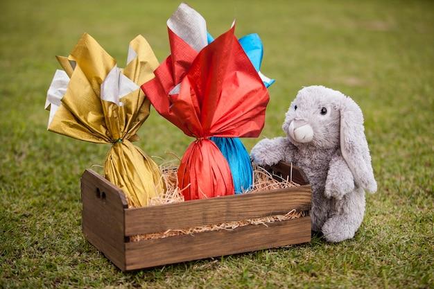 Um coelho de pelúcia segurando uma cesta de ovos de páscoas brasileiras na grama